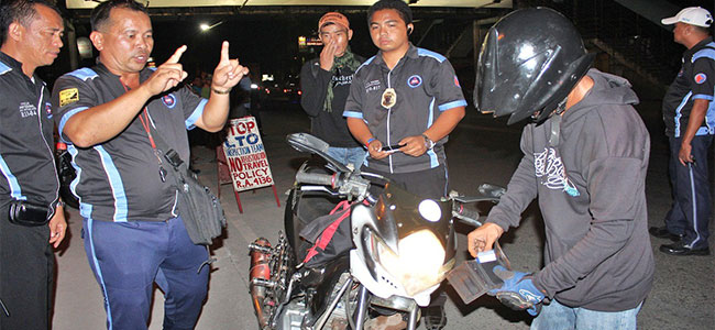 CAUGHT. Members of a composite team of law enforcers surround a motorcycle driver as they ask to see his driving license and vehicle registration papers at a checkpoint in Puerto, this city, on Thursday night. The Land Transportation Office says the operation resulted in the apprehension of 211 traffic violators in just four hours.  The team is composed of members of the LTO, Highway Patrol, Cocpo Traffic Division and the Puerto police. Story on page 14  (PHOTO BY NITZ ARANCON)