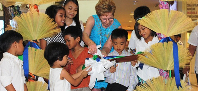 """20 YEARS. Australian Jean Langworthy of the Disaster Aid International of the Rotary guides children in cutting the ceremonial ribbon during the launch of Balay Mindanao Foundation's photo exhibit at Centrio mall here. The non-government organization is celebrating its 20th anniversary, and the """"local victories of barangays."""" (PHOTO BY NITZ ARANCON)"""