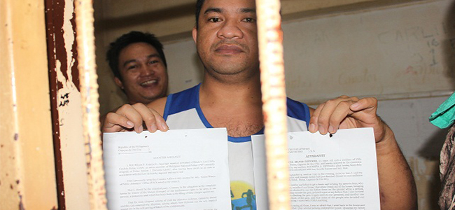 FIGHTING BACK. Drug suspect PO3 Wilson Estenzo shows a copy of his counter-affidavit against agents of the Philippine Drug Enforcement Agency behind bars. Estenzo has sought a preliminary investigation into his case. (PHOTO BY NITZ ARANCON)