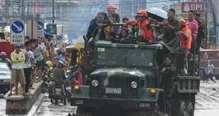 HELPING THE STRANDED. An Army truck is used to fetch stranded commuters along the flooded CM Recto Avenue here yesterday morning, a day after a heavy downpour. (PHOTO BY FROILAN GALLARDO)