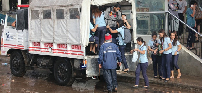 FINALLY, TRANSPORTATION. Stranded students of the University of Science and Technology of Southern Philippines (formerly Must) finally ride a city hall disaster response team truck after spending the night in their school. The campus was surrounded by floodwaters.  (PHOTO BY NITZ ARANCON)